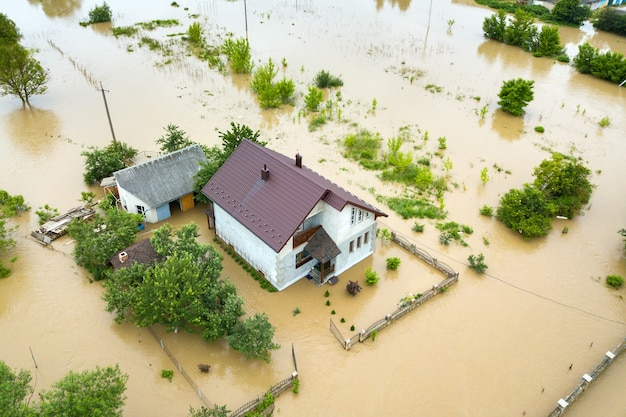 Aerial view of flooded house with dirty water all around it