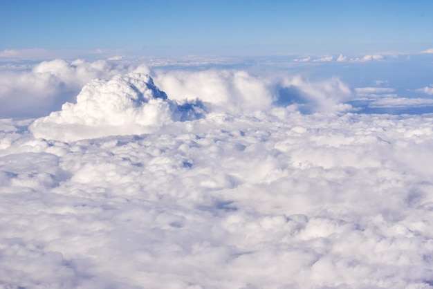 Aerial view of fluffy clouds in a stratosphere from airplane window