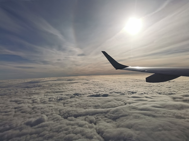 Aerial view of fluffy clouds with the sun under the wing of the plane