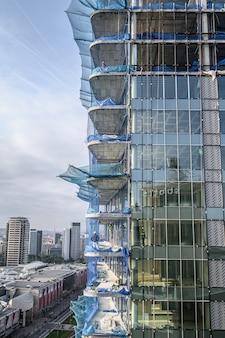 Вид с воздуха на строительство небоскреба, строительных лесов, шлагбаумов, рабочих. 03.01.2020 барселона, испания