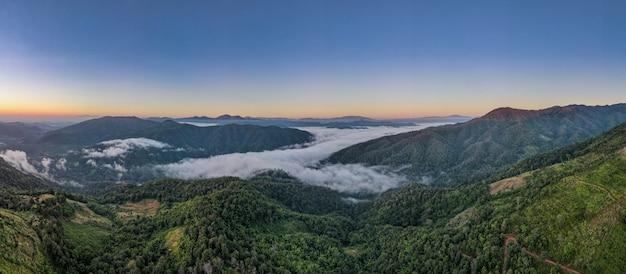 Вид с воздуха на лес в утреннем тумане, дышащие горы, солнце в утреннем тумане