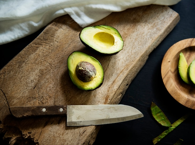 Aerial view of fresh avocado on wooden cut board