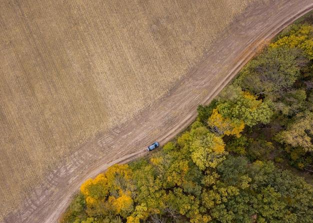 농업 분야와 산림 지역에 걸쳐 비포장 도로 위의 무인 항공기에서 공중보기.