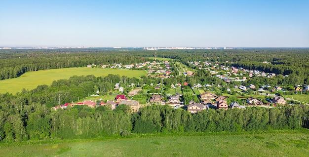 Вид с воздуха с дрона на сельскую деревню, поля и леса вокруг