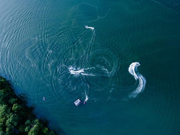水上でジェットスキーに乗る人々のドローンからの空撮