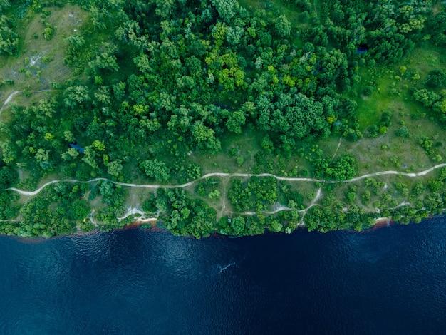 여름에 푸른 초원 사이의 신선한 강에 있는 무인 항공기에서 공중 보기