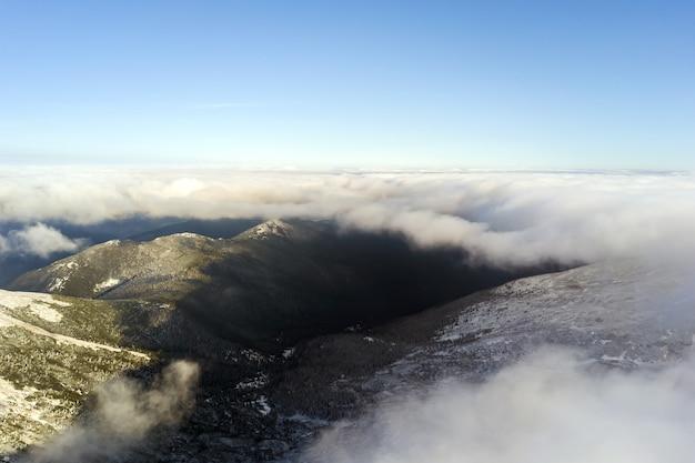 밝고 화창한 날 눈 덮인 산 정상을 덮고 있는 하얀 푹신한 구름 위에서 공중 전망.