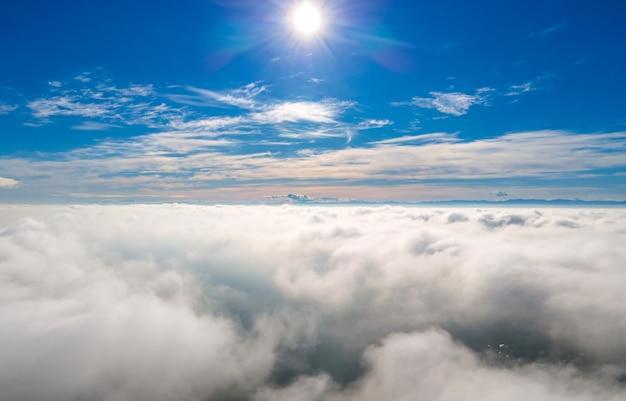 明るい晴れた日の白いふくらんでいる雲の上からの空中写真。