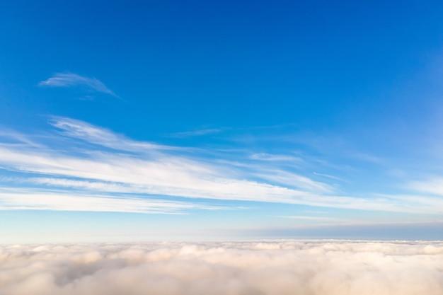 밝고 화창한 날에 흰색 푹신한 구름 위에서 공중 볼 수 있습니다.