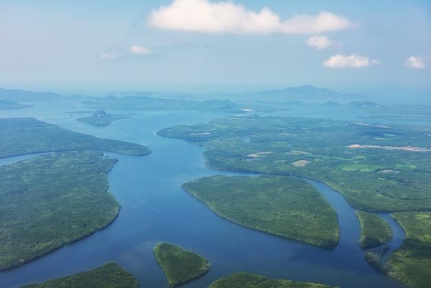 Вид с воздуха из окна самолета на естественный остров краби, карстовые известняковые горы и андаманское море летом, таиланд. известное туристическое направление на юге таиланда или сиама.