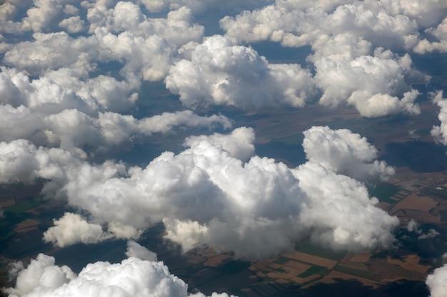 明るい晴れた日の白いふくらんでいる雲の飛行機の窓からの空撮。