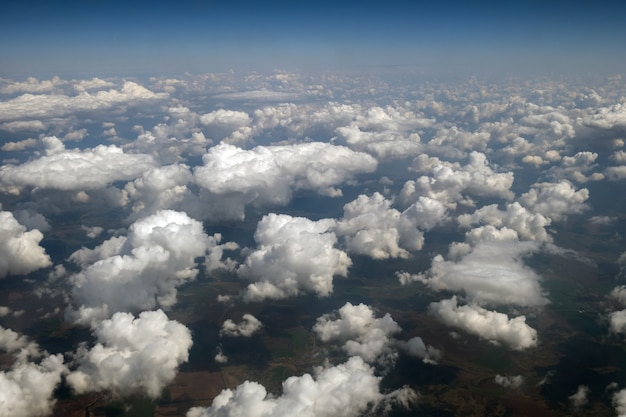 Aerial view from airplane window of white puffy clouds on bright sunny day.