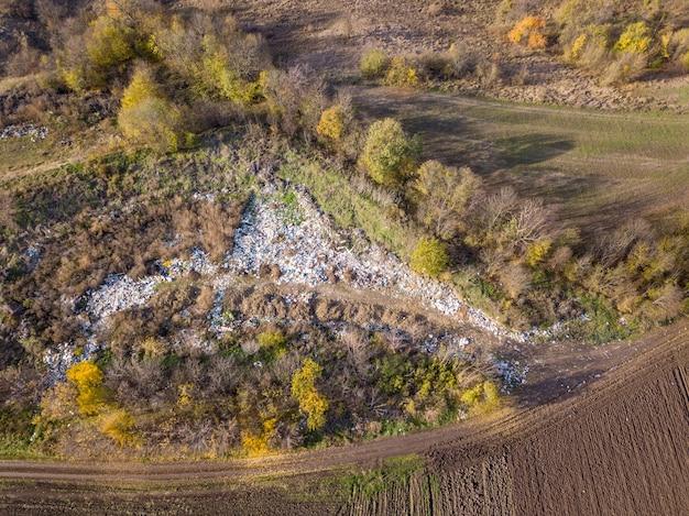 Вид с воздуха с дрона над свалкой в окружении деревьев.