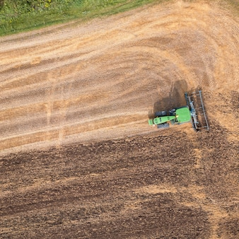 Aerial view from the drone of the field after harvest. plowing the ground after harvesting on the field in the autumn time.