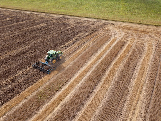 Aerial view from the drone of the field after harvest. the tractor plowing the soil after harvesting on the field - preparation of the soil to sowing work.