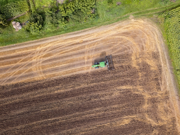 Aerial view from the drone of the field after harvest. the tractor plows the field, preparing the soil for agricultural work.