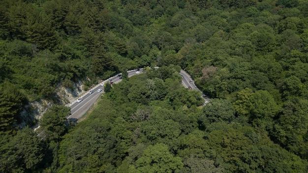 러시아의 녹색 숲이 있는 산에 차가 있는 곡선 도로의 무인 항공기에서 공중 보기
