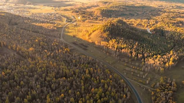 村を背景に、川、秋の森、丘、アスファルト道路のドローンからの空撮。
