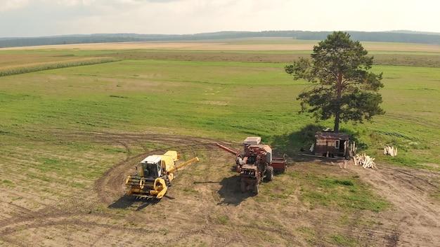 Вид с воздуха с дрона двух сельскохозяйственных комбайнов и комбайнов, стоящих на широком коричневом поле между одиноким зеленым деревом и грунтовой дорогой.