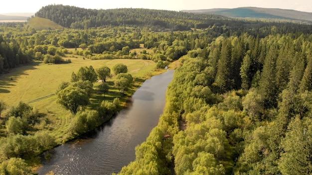 Вид с воздуха с дрона на горную реку, поле, лес и путь. природа пейзаж