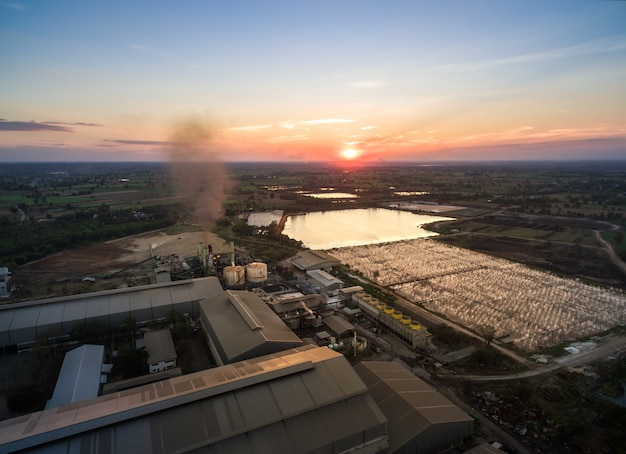 Aerial view from drone sugar factory with waste water treatment at sunset.