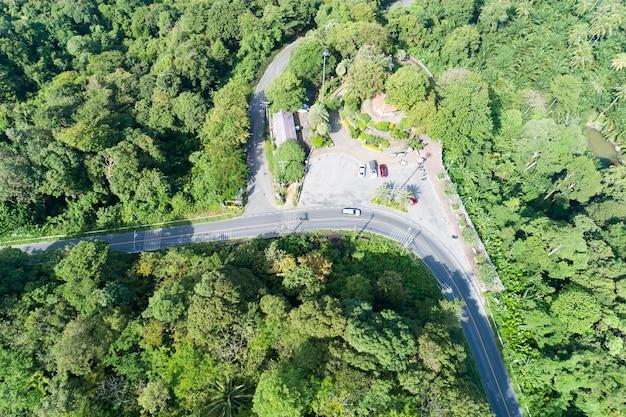 태국 푸켓의 녹색 숲이 있는 아스팔트 도로 곡선의 드론 평면도에서 공중 보기