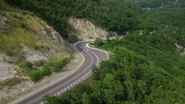 Вид с воздуха с дрона - извилистая дорога с высокого горного перевала в сочи, россия.