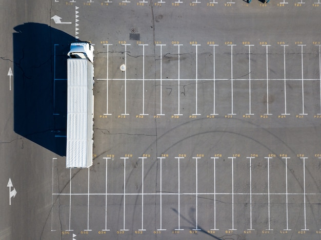 Aerial view from a flying drones of parking lot, marking parking spaces with a long truck and long shadows from it on a summer day. top view.