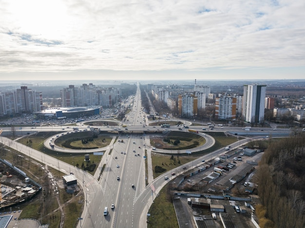 현대 주택과 가을 날 하늘을 배경으로 한 quatrefoil 형태의 도로 인터체인지가있는 오데사 광장의 교차점과 도시의 무인 항공기에서 공중보기. 키예프, 우크라이나