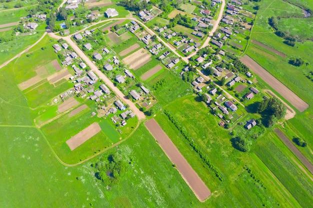 野菜作物のフィールドを持つ田舎の村の高さからの空撮