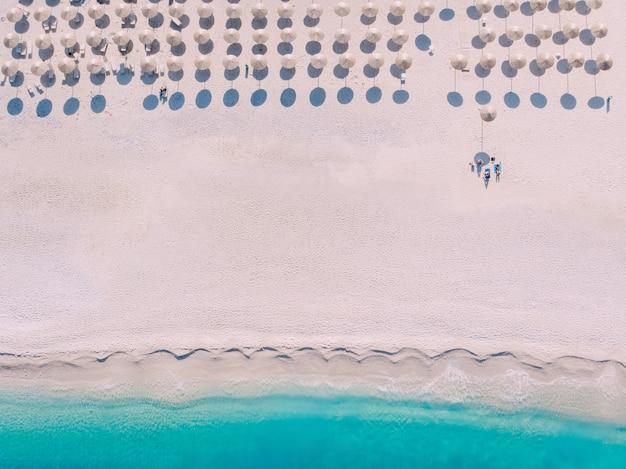 美しいターコイズブルーの海のほとりに傘とラウンジャーを備えたビーチまでの空中写真。