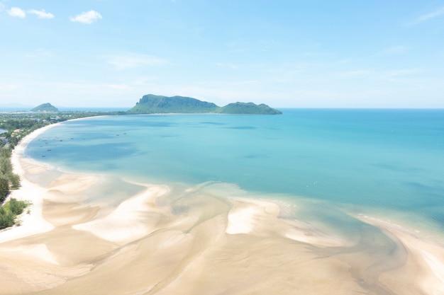 視点からの空撮。穏やかな日に青い空と海とビーチ。