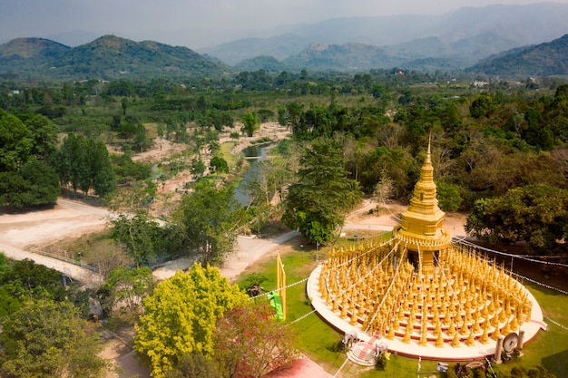 Aerial view of gold buddist pagoda in saraburi central of thailand