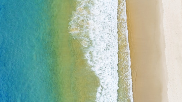 Aerial view of the gradient color of ocean surface with waves washing on the coast of the andaman ocean amazing top down nature landscape seascape view beautiful for travel background and website.