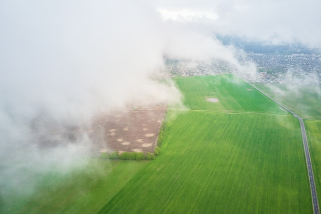 Aerial view of green field with fluffy clouds