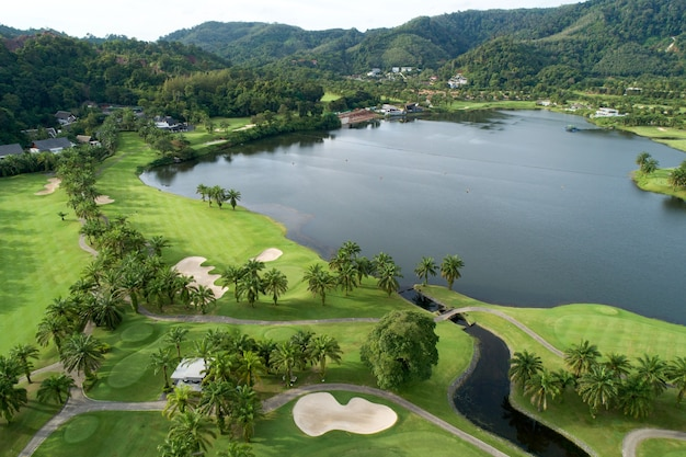Aerial view of the green golf course in thailand beautiful green grass and trees on a golf field with fairway and putting green in summer season.