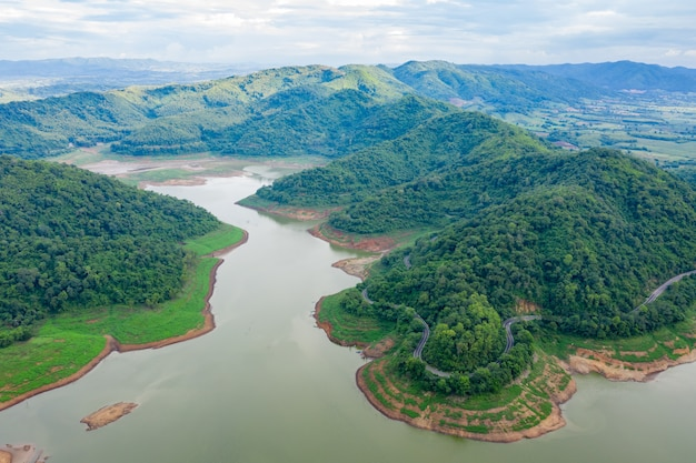 Aerial above view green mountain forest and dam reservoir river in the rain season and curved road on the hill connecting countryside