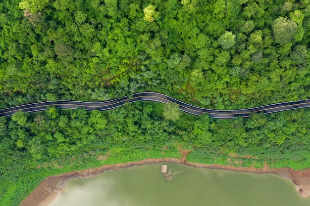 Aerial above view green mountain forest and river in the rain season and curved road on the hill connecting countryside