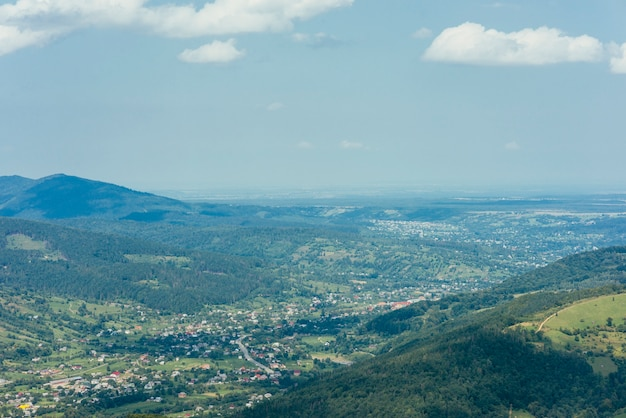 Aerial view of green mountain valley with town