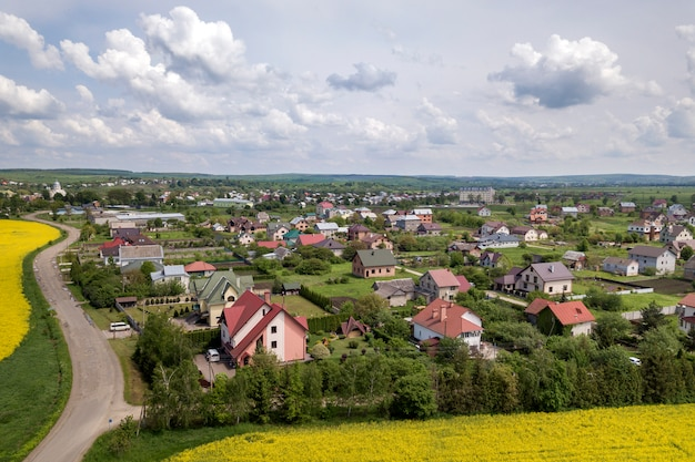 Aerial view of ground road in green fields with blooming rapeseed plants, suburb houses on horizon