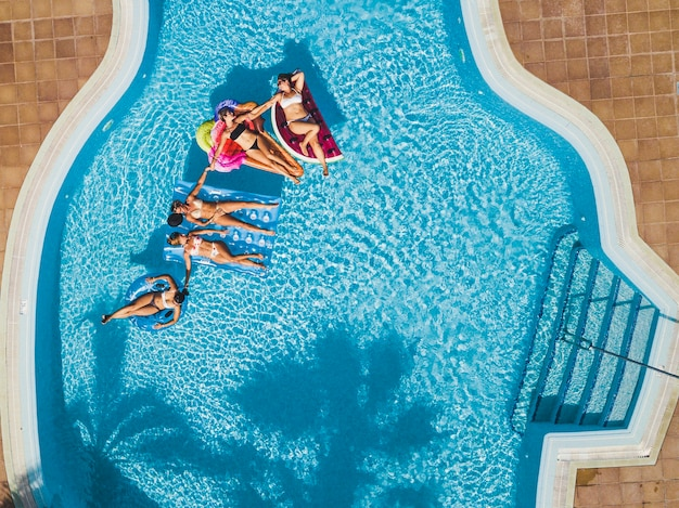 Aerial view of group of female people enjoy summer holiday vacation at the pool laying on coloured trendy lilo