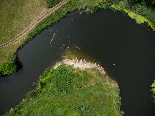 Aerial view of a group of kayaks traveling on a forest river on a summer day