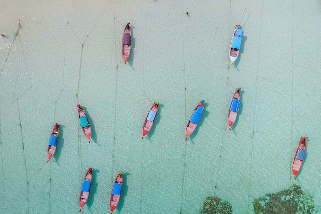 Aerial view over group of long tail boats with beautiful sea and beach