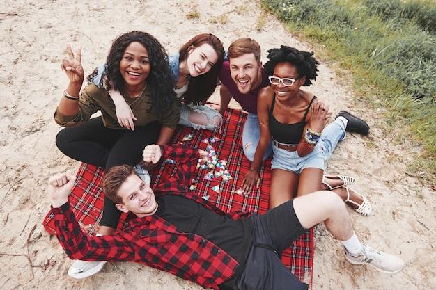 С высоты птичьего полета. группа людей устраивает пикник на пляже. друзья веселятся в выходные.
