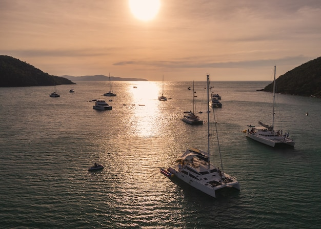 Aerial view of group of private yacht sailing on tropical sea at the sunset