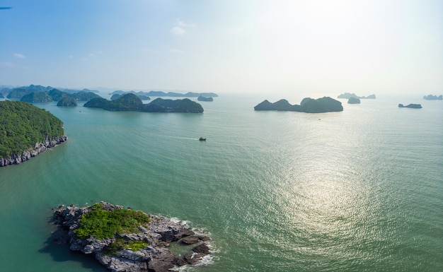 Aerial view of ha long bay from cat ba island, famous tourism destination in vietnam. scenic blue sky with clouds, limestone rock peaks in the sea at the horizon.
