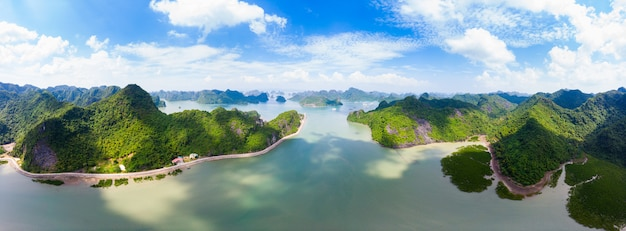 Aerial view of ha long from bay cat ba island, unique limestone rock islands and karst formation peaks in the sea, famous tourism destination in vietnam. scenic blue sky.