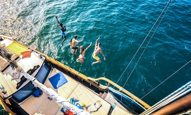 Aerial view of happy friends jumping from sailboat on ocean trip