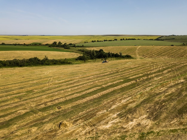 Aerial view to harvested field with straw bales in summer