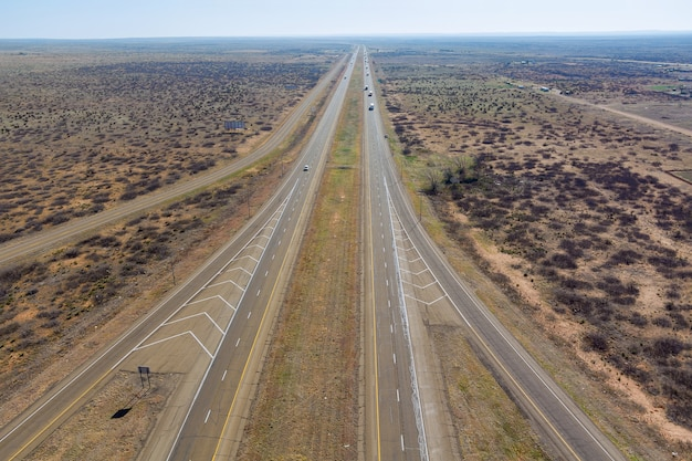 米国ニューメキシコ州サンジョンの近くに向かって砂漠の風景を通る長い車線の道路のある空中写真高速道路